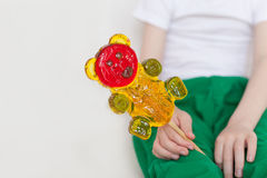 Caramelo en un palillo en la mano del ` s del niño imágenes de archivo libres de regalías