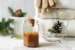 Caramelo en un tarro de cristal en un fondo del invierno con una manta o un jersey, guantes, una taza, ramas spruce y conos imagen de archivo