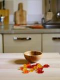 Caramelo gomoso colorido del oso en la tabla de madera en fondo de la cocina Foto de archivo libre de regalías