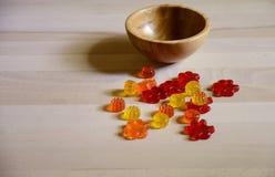 Caramelo gomoso del oso en la tabla de madera en fondo de la cocina Foto de archivo