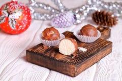 Caramelo hecho a mano del coco del chocolate en la tabla de madera con la Navidad imagen de archivo libre de regalías