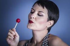 Caramelo, mujer joven feliz con el lollypop en su boca en el CCB azul Fotografía de archivo libre de regalías