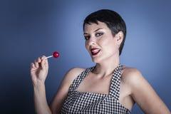 Caramelo, mujer joven feliz con el lollypop en su boca en el CCB azul Fotografía de archivo