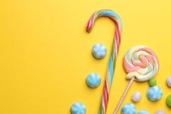Caramelo redondo multicolor y piruletas coloreadas en un fondo brillante amarillo fotos de archivo libres de regalías