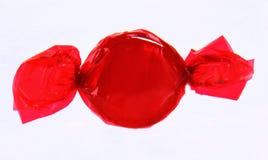 Caramelo rojo en envoltura en el fondo blanco Imagen de archivo