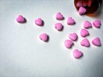 Caramelo rosado de la forma del corazón con el envase marrón en el fondo blanco Imagenes de archivo
