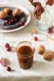 Caramelo salado en un vidrio en un fondo del otoño de hojas, de nueces y de manzanas Estilo rústico fotos de archivo