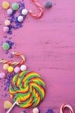 Caramelo y piruleta clasificados en la tabla de madera rosada Fotos de archivo