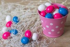 Caramelos coloreados en cubo rosado Foto de archivo