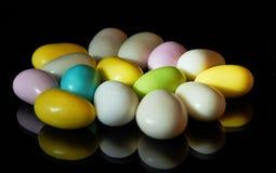 Caramelos coloreados multi aislados en negro imagen de archivo