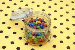 Caramelos coloridos en el tarro de cristal Foto de archivo