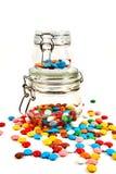 Caramelos coloridos en el tarro de cristal dispersado aislado en blanco foto de archivo