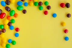 Caramelos coloridos en fondo amarillo imagenes de archivo