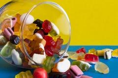 Caramelos coloridos en tarro en fondo azul imagen de archivo