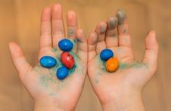 Caramelos coloridos sostenidos en manos del niño fotos de archivo