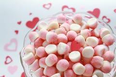 Caramelos de azúcar con el corazón de una tarjeta del día de San Valentín en un fondo romántico Foto de archivo libre de regalías