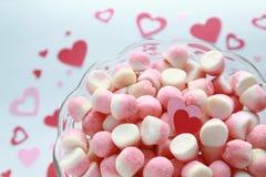 Caramelos de azúcar con un par de los corazones de la tarjeta del día de San Valentín en un fondo romántico Fotografía de archivo libre de regalías