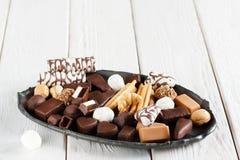 Caramelos de chocolate clasificados en la placa negra Fotografía de archivo libre de regalías