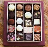 Caramelos de chocolate clasificados en una tabla de madera Foto de archivo