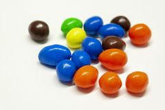 Caramelos de chocolate coloridos en el fondo blanco imagenes de archivo