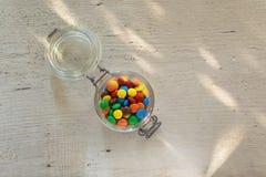 Caramelos de chocolate coloridos en el tarro de cristal Imagenes de archivo