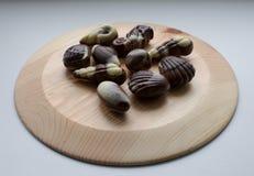 Caramelos de chocolate en la placa de madera Imagenes de archivo