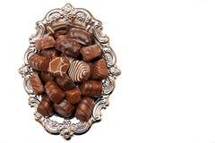 Caramelos de chocolate en un disco de plata Foto de archivo libre de regalías