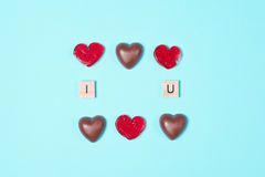 Caramelos de chocolate y piruletas rojas con las letras de madera Fotografía de archivo