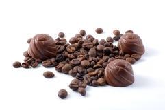 Caramelos de Chokolate y granos de café dispersados imagenes de archivo