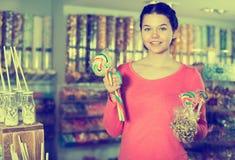 Caramelos de compra de la muchacha en la tienda Fotografía de archivo