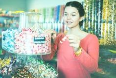 Caramelos de compra de la muchacha en la tienda Imagenes de archivo