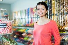 Caramelos de compra de la muchacha en la tienda Imágenes de archivo libres de regalías