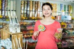 Caramelos de compra de la muchacha en la tienda Foto de archivo