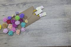 Caramelos de la melcocha en el sobre adornado con las rosas Presente, sorpresa, conceptos del amor Fotografía de archivo libre de regalías