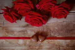 Caramelos del corazón del chocolate del presente del día del ` s de la tarjeta del día de San Valentín y rosas rojas Fotografía de archivo libre de regalías