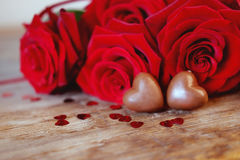 Caramelos del corazón del chocolate del presente del día del ` s de la tarjeta del día de San Valentín y rosas rojas Imagenes de archivo