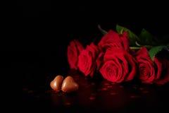 Caramelos del corazón del chocolate del presente del día del ` s de la tarjeta del día de San Valentín y rosas rojas Imagen de archivo