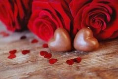 Caramelos del corazón del chocolate del presente del día del ` s de la tarjeta del día de San Valentín y rosas rojas Foto de archivo
