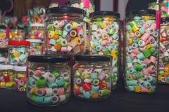 Caramelos en los tarros de cristal en tienda del caramelo Foto de archivo