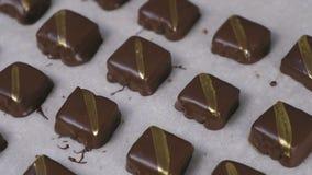 Caramelos hechos a mano de los hocolates sabrosos hermosos con las rayas de oro en el papel de los panaderos Opini?n del primer almacen de video