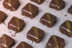 Caramelos hechos a mano de los hocolates sabrosos hermosos con las rayas de oro en el papel de los panaderos Opini?n del primer fotos de archivo