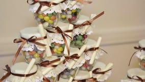 Caramelos multicolores en los tarros de cristal para las huéspedes del banquete de boda almacen de metraje de vídeo
