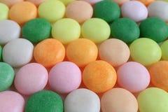 Caramelos redondos coloridos alineados con el foco selectivo para el fondo Fotos de archivo