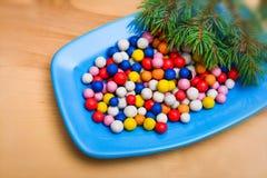 Caramelos redondos coloridos de la Navidad en una placa Foto de archivo libre de regalías