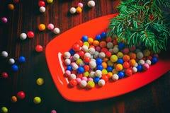 Caramelos redondos coloridos de la Navidad en una placa Imágenes de archivo libres de regalías