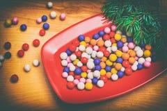 Caramelos redondos coloridos de la Navidad en una placa Imagen de archivo