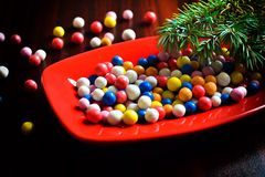 Caramelos redondos coloridos de la Navidad en una placa Imagen de archivo libre de regalías