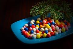 Caramelos redondos coloridos de la Navidad en una placa Fotografía de archivo