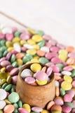 Caramelos redondos coloridos en la taza de madera Fotografía de archivo