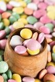 Caramelos redondos coloridos en la taza de madera Imágenes de archivo libres de regalías